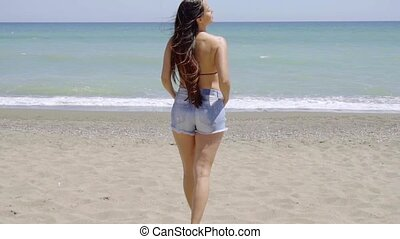 Trendy shapely young woman standing on a each