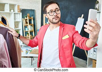 Trendy stylist taking photo in atelier