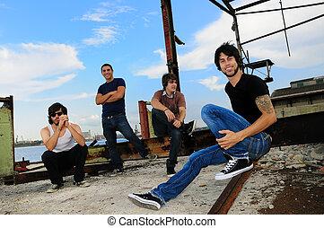 Portrait of casual team of friends posing on grunge urban scene