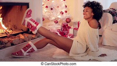 Trendy vivacious woman wearing Christmas booties warming her...