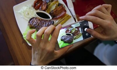 Trendy woman in a restaurant make photo of food with mobile...