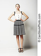 Trendy Woman in Stripped Skirt and T-Shirt standing. Urban Clothing Collection