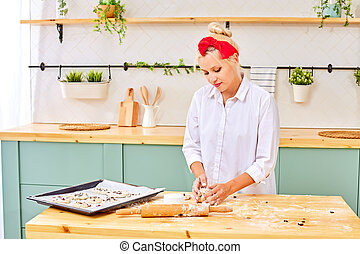 Trendy woman preparing pastry on kitchen table