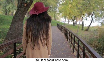 Trendy woman walking on wooden bridge in park