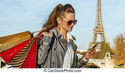 trendy woman with shopping bags writing sms near Eiffel...