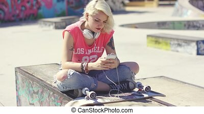 Trendy young blond woman at a skate park sitting on a...