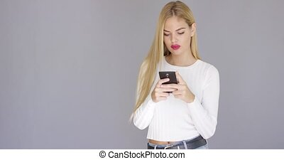 Trendy young blond woman checking her mobile