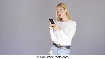 Trendy young blond woman checking her mobile laughing as she...