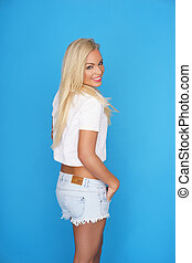Trendy young blond woman in denim shorts