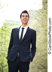 Trendy young businessman smiling outdoors