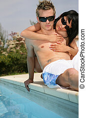 Trendy young couple laying down next to swimming pool