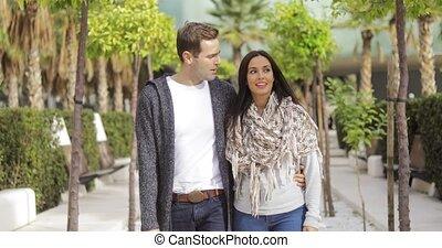 Trendy young couple walking along a promenade