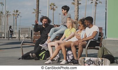 Trendy young friends on bench on street - Modern young...