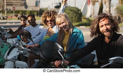 Trendy young friends on scooters waving at camera - Group of...