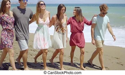 Trendy young friends strolling barefoot on a beach with...