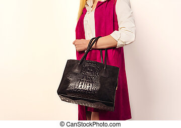 Trendy young girl in a vest of fuchsia holding big black handbag