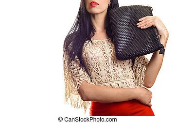Trendy young girl in red skirt holding black leather handbag