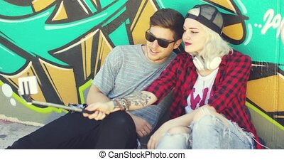 Trendy young hipster couple taking a selfie