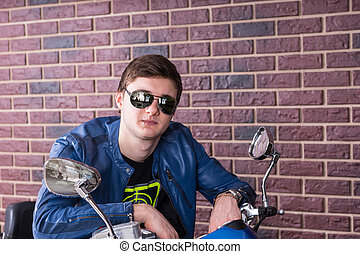 Trendy young man on a motorbike