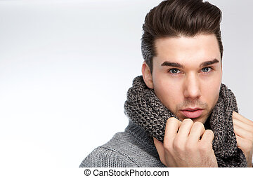 Close up portrait of a trendy young man posing with gray wool scarf