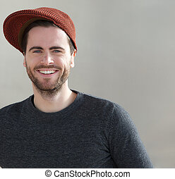 Trendy young man smiling with hat