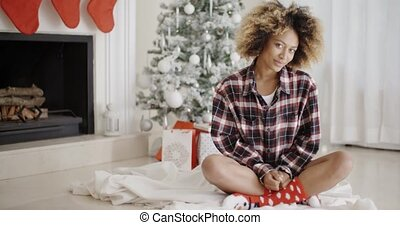 Trendy young woman in front of a Christmas tree