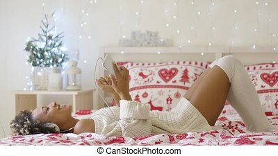 Trendy young woman listening to Christmas music lying on her...