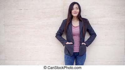 Trendy young woman posing against a wall