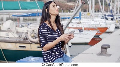 Trendy young woman relaxing at a marine harbour