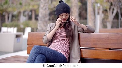 Trendy young woman relaxing on a park bench