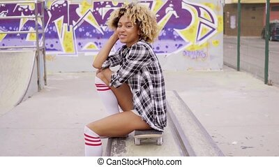 Trendy young woman sitting on a skateboard