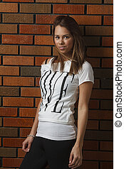 trendy young woman - twenty something girl leaning against a...