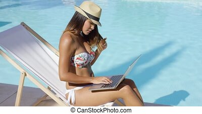 Trendy young woman using a laptop at the pool