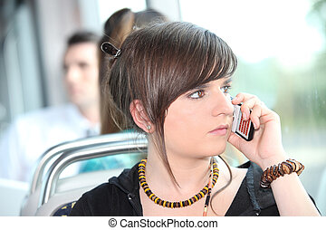 Trendy young woman using her cellphone on a tram