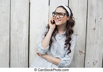 Trendy young woman with stylish glasses having phone call ...