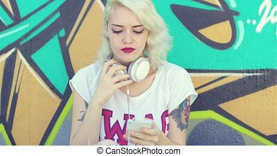 Trendy young woman with tattoos listening to music