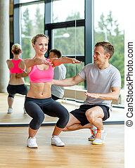 trener, kobieta, sala gimnastyczna, wykonując, uśmiechanie ...