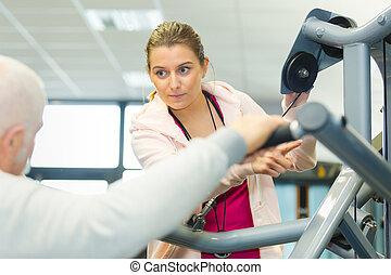 trener stosowności, pomagając, na, starszy człowiek, w sali gimnastycznej