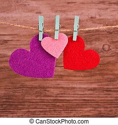 tres, coloreado, corazones, ahorcadura, hilo, en, de madera, plano de fondo