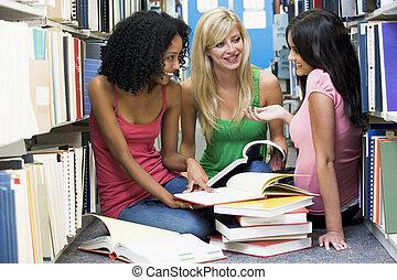 tres mujeres, sentar piso, en, biblioteca, con, libros