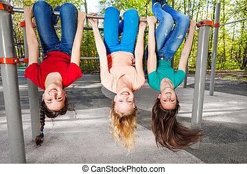 tres niñas, el colgar al revés, en, brachiating, barra