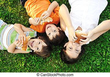 tres niños, colocar, en, hierba verde, en, suelo, y, comida,...