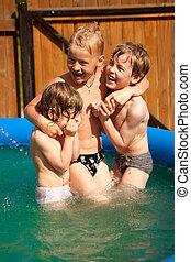 tres niños, juego, en, inflable, piscina