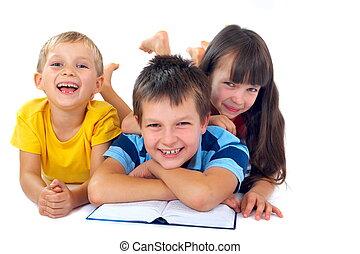 tres, niños, lectura, en, piso