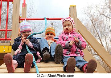 tres niños, sentarse, en, artificial, colina, en, patio de recreo
