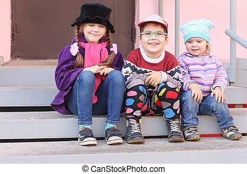 tres, poco, niños, en, brillante, ropa, sentar escalera, en, el, entrada