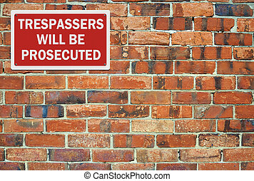 'Trespassers' will be prosecuted' sign, against brick wall....