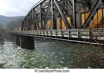 A view of a coal-town train on a trestle goving over a river on a rainy day.