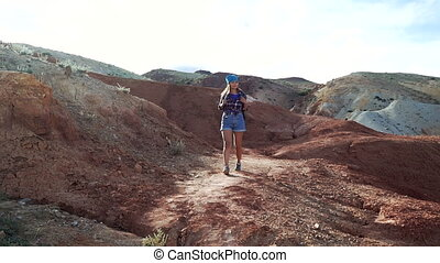 Treveler girl is walking in a scenic landscape in the middle of the red stone mountains. Front view