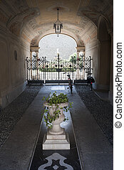 Treviglio (Bergamo, Lombardy, Italy), entrance of historic palace with plants and two bicycles